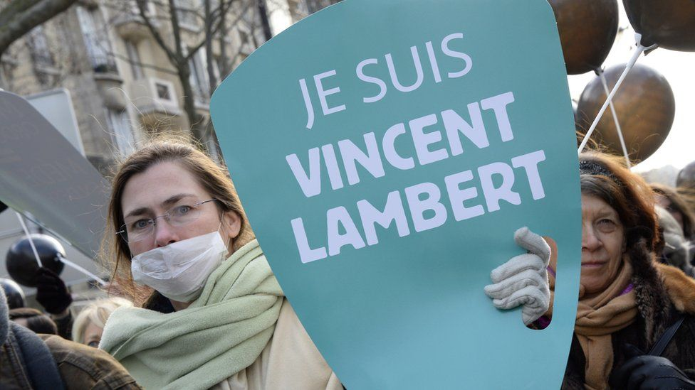 "French woman holds a ""Je Suis (I am) Vincent Lambert"" sign"