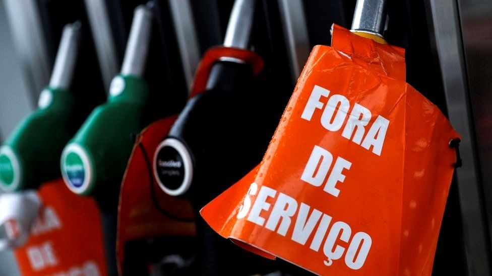 """A close-up photograph shows fuel pump nozzles docked in their pumping station. One is wrapped in an orange sign reading """"For de Servico"""" - the Portuguese for out of service"""