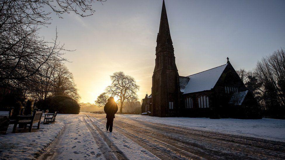 A person walks through Allerton Cemetery near Liverpool on Thursday