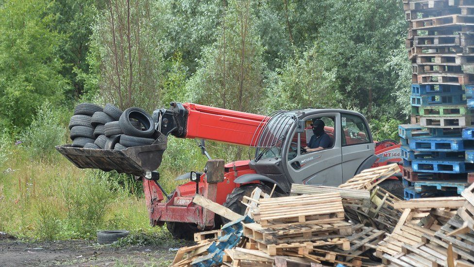 A man driving a telehandler removes tyres from the bonfire on London Road in Belfast