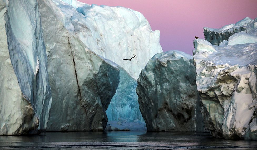 Icebergs are seen at the at the mouth of the Jakobshavns ice fjord during sunset near Ilulissat, Greenland, in September 2021