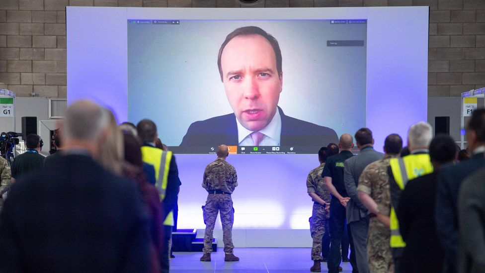 People watch as a giant screen displays an image of Health Secretary Matt Hancock speaking via video-link during the official opening of the NHS Nightingale Hospital Birmingham.