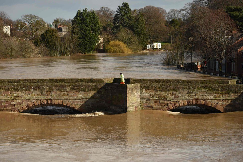 A man walks on the Old Bridge in Hereford as the waters of the swollen River Wye fill the arches