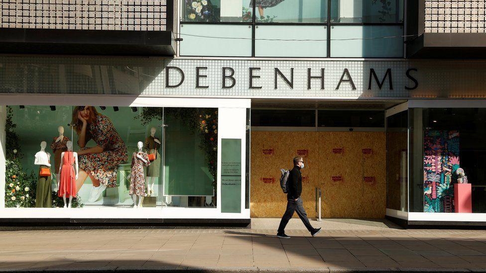 Man walking past a Debenhams store