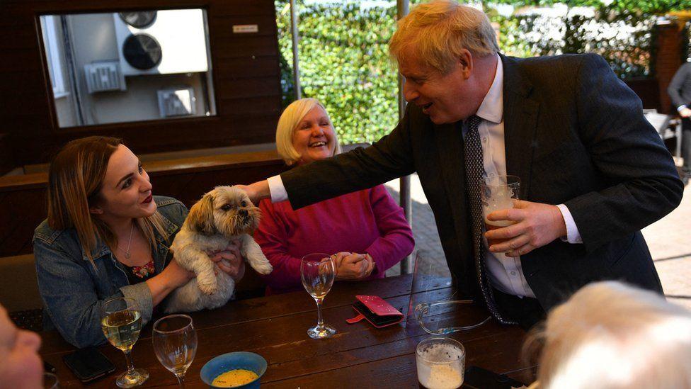 Boris Johnson pets' a customer's dog at a beer garden