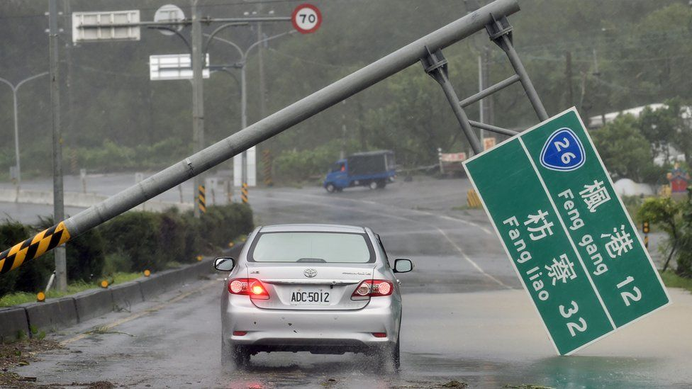 A car drives pass a collapsed traffic sign, toppled by strong winds of typhoon Meranti, as it slashes southern Taiwan on September 14, 2016.