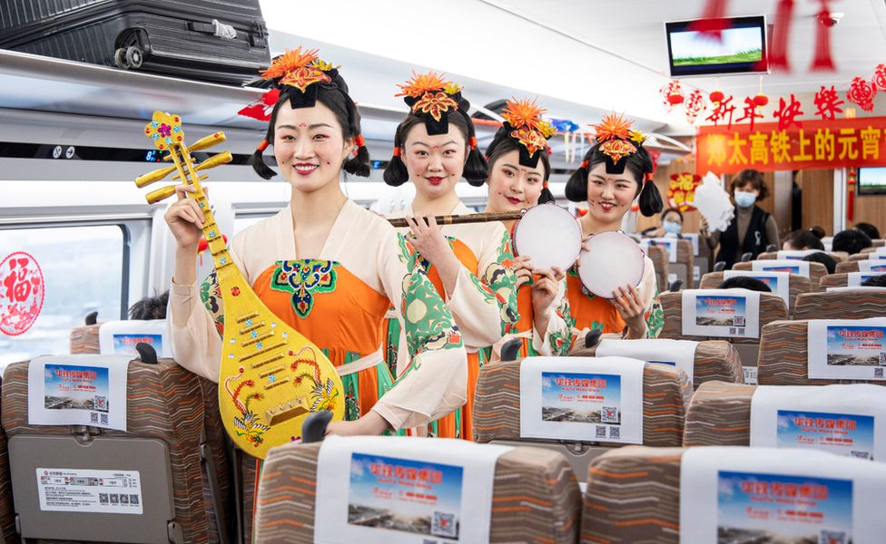Train attendants dressed in historical costumes and holding musical instruments on board a train in Zhengzhou Photo: 26 February 2021