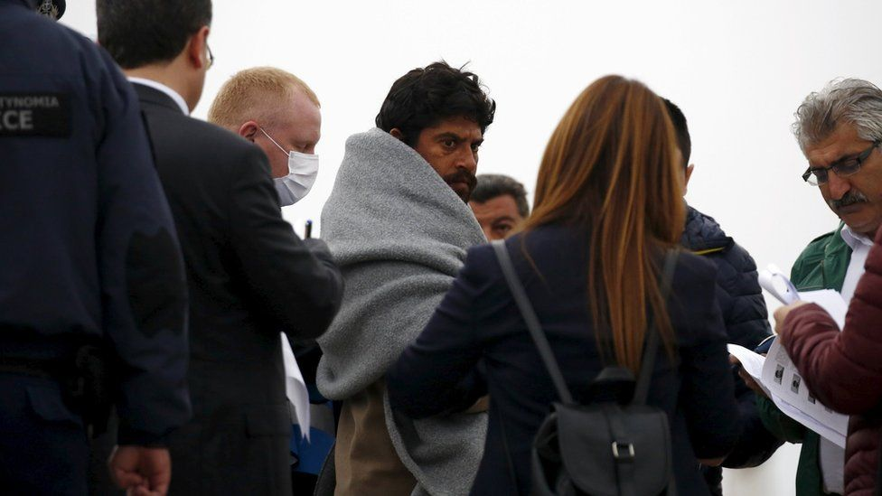 A deportee is escorted aboard the ferry on Lesbos, 8 April