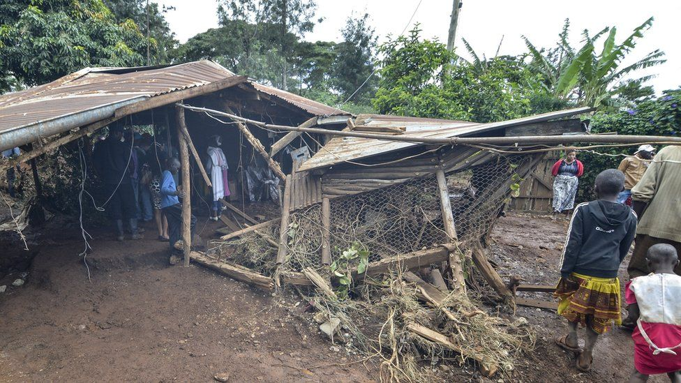 Residents walk next to a house destroyed by water that leaked from Petal dam after bursting its banks near the town of Solai, in Nakuru County on 10 May 2018.