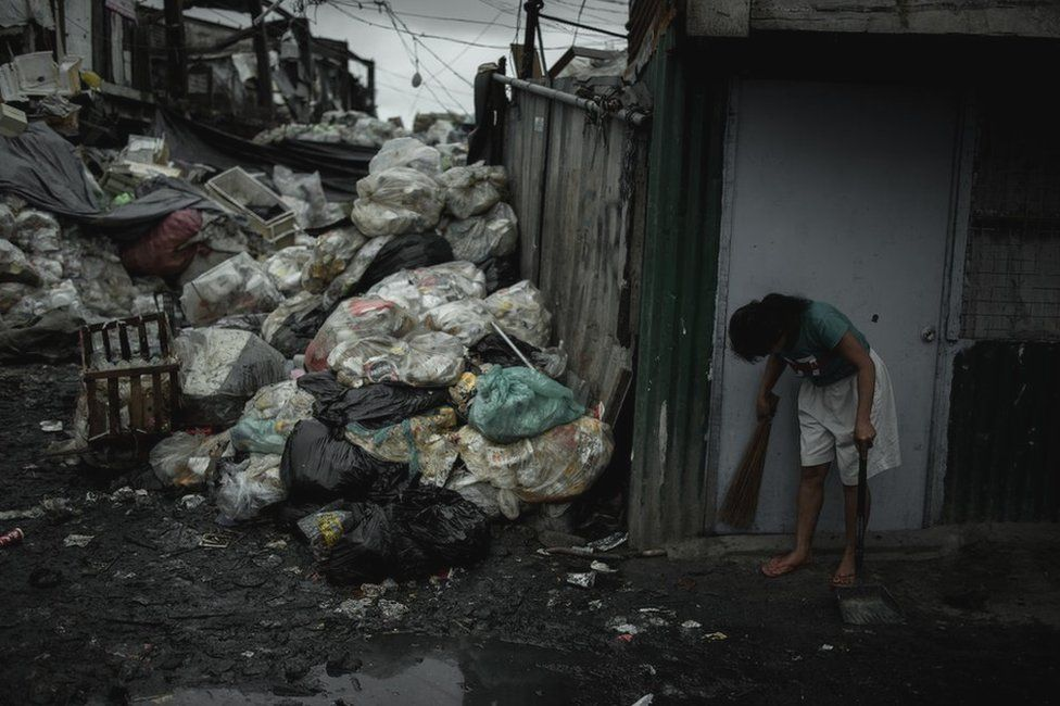 A woman sweeping the front of her house in Happyland a dump site in Tondo, Manila