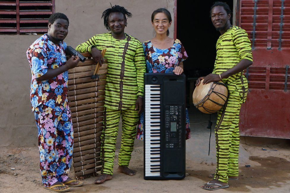 Maboudou Sanou, Boureima Sanou, Keiko Fujiie and Ibrahim Dembélé pose for a photograph outside the house Fujiie shares with Maboudou Sanou and his family in Ouagadougou. The musicians are from a griot family from the town of Nouna in Western Burkina Faso, in which musical traditions have been handed down from generation to generation. The group rehearse Monday to Friday.