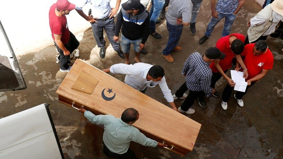 Relatives carry a coffin containing the body of an immigrant who drowned when a boat sank, at a hospital morgue in Sfax, Tunisia, on 4 June 2018