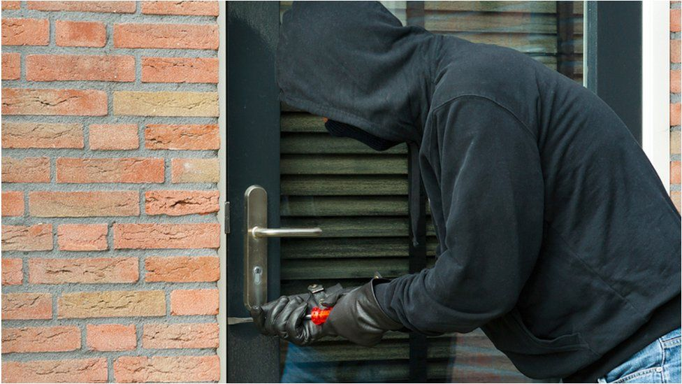 Hooded man attempting break-in