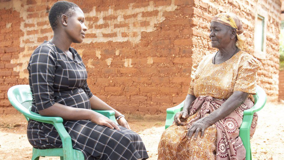 Birth attendant and pregnant woman talking outside the house