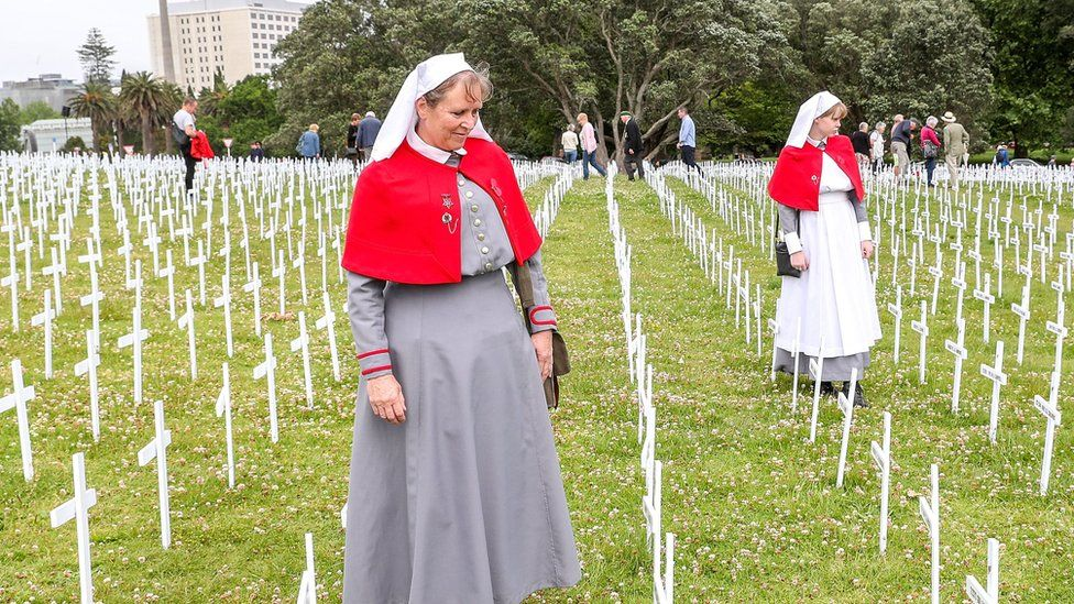 Tracey (L) and Katherine Meeten, dressed as nurses, look at crosses in the Fields of Remembrance in Auckland, New Zealand