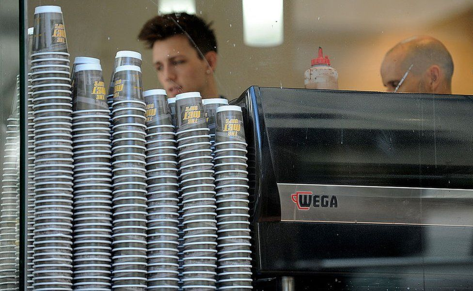 Take-away coffee cups are displayed alongside a coffee machine at the 'Met Cafe', one of the most popular cafes in the central business district of Sydney on April 20, 2010.