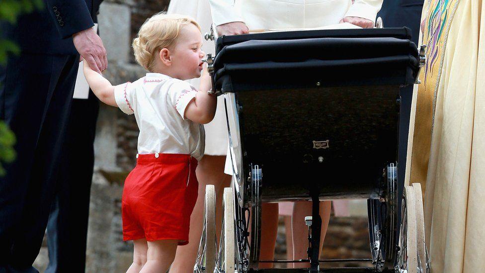 Prince George peers into his sister's pram