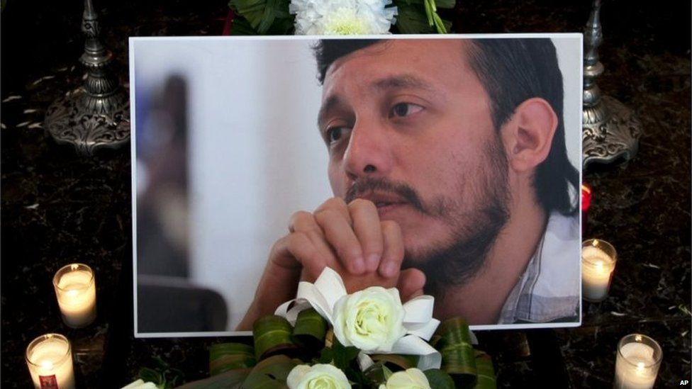 A photograph of murdered photojournalist Ruben Espinosa sits among flowers and candles in front of his casket inside a funeral home before his wake begins in Mexico City, Monday on 3 August, 2015.