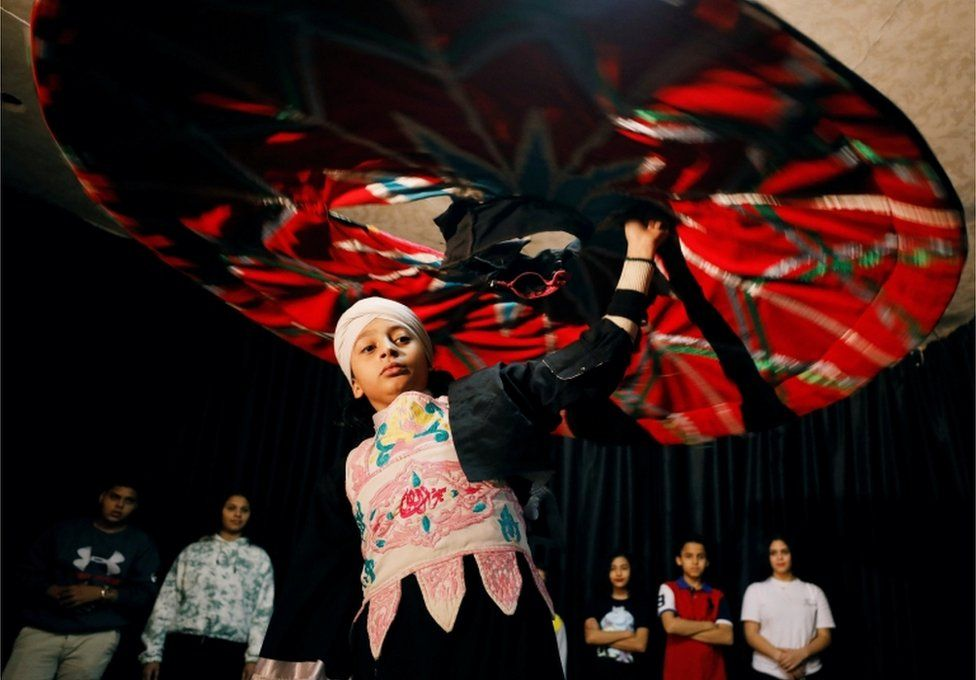 A boy spins a large, multi-coloured skirt above his head.