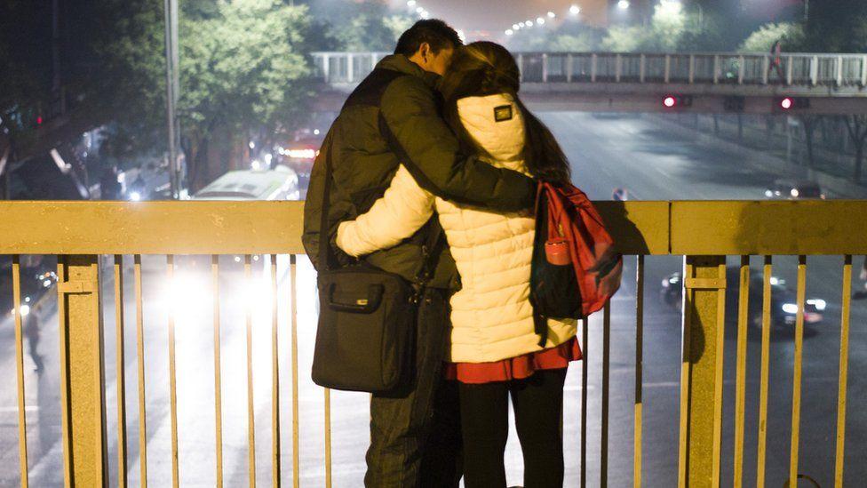 Couple embrace on a bridge