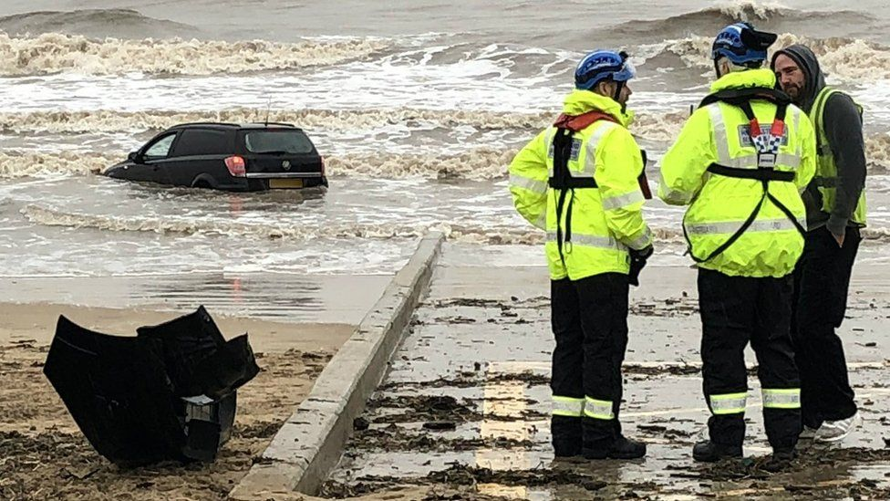 Coastguards on the beach by the stranded vehicle at Blackpool