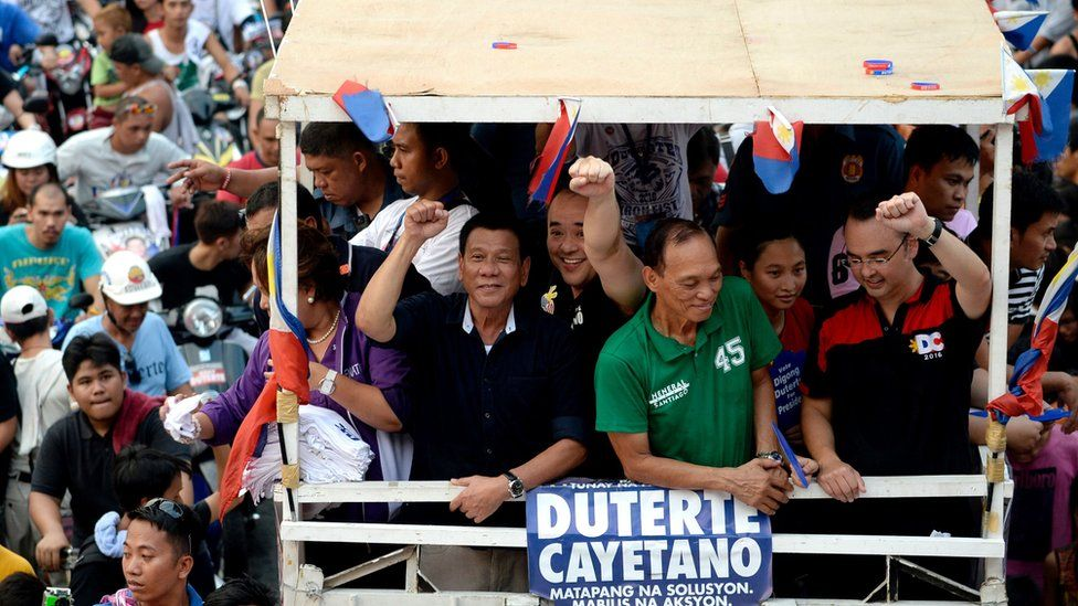 Rodrigo Duterte (centre, in black) gestures to the crowd from the top of a packed campaign bus driving through crowds in Manila on 27 April