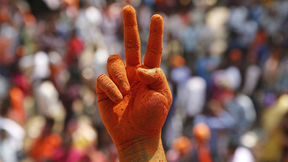A BJP supporter makes a victory sign with saffron-coloured fingers, Lucknow, Uttar Pradesh (11 March)