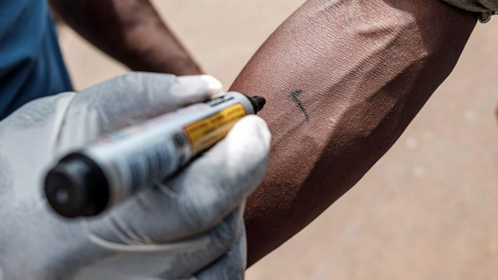 A Red Cross volunteer marks a person's arm with a tick at Nakasero market in Kampala, Uganda - Wednesday 1 April 2020