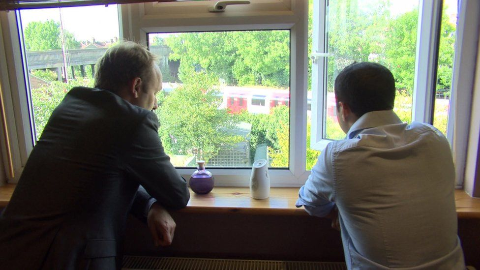 Tom Edwards and resident Ash Khan look out of his window at the nearby tracks