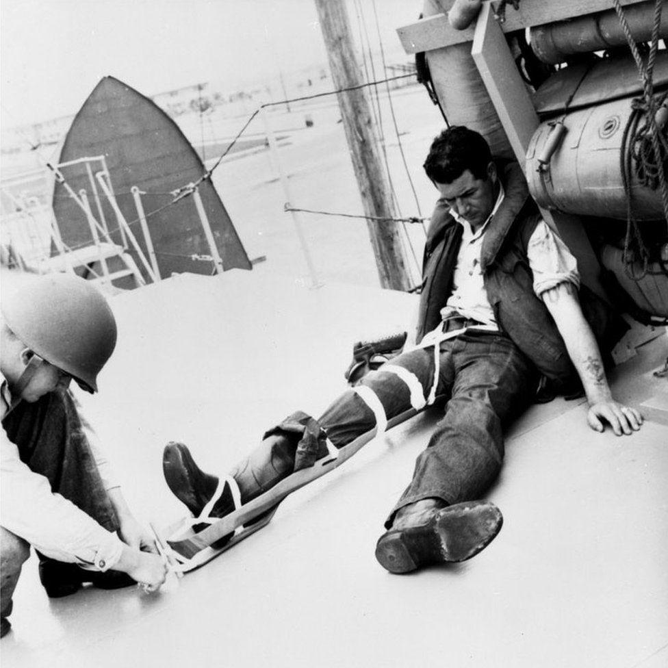 An injured American serviceman is treated with an Eames leg splint