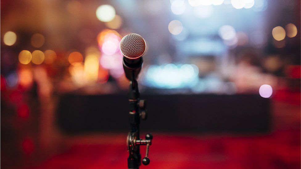 A microphone on a stage waiting for a speaker, with audience in blurred background