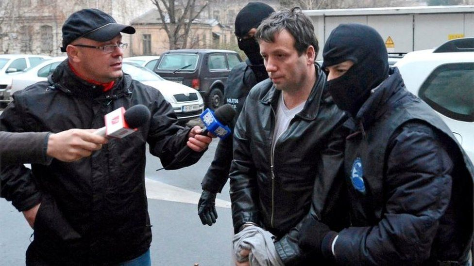 Marcel Lazar Lehel is escorted by masked policemen in Bucharest, after being arrested on 22 January, 2014.