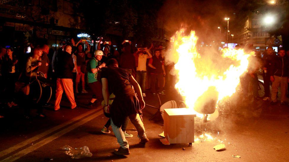 Protestors burn furniture taken out of the demolished President's office in downtown Skopje, Macedonia, late Wednesday, April 13, 2016.