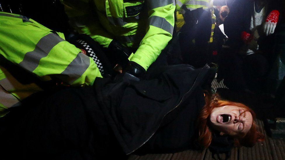 Police detain a woman as people gather at a memorial site in Clapham Common