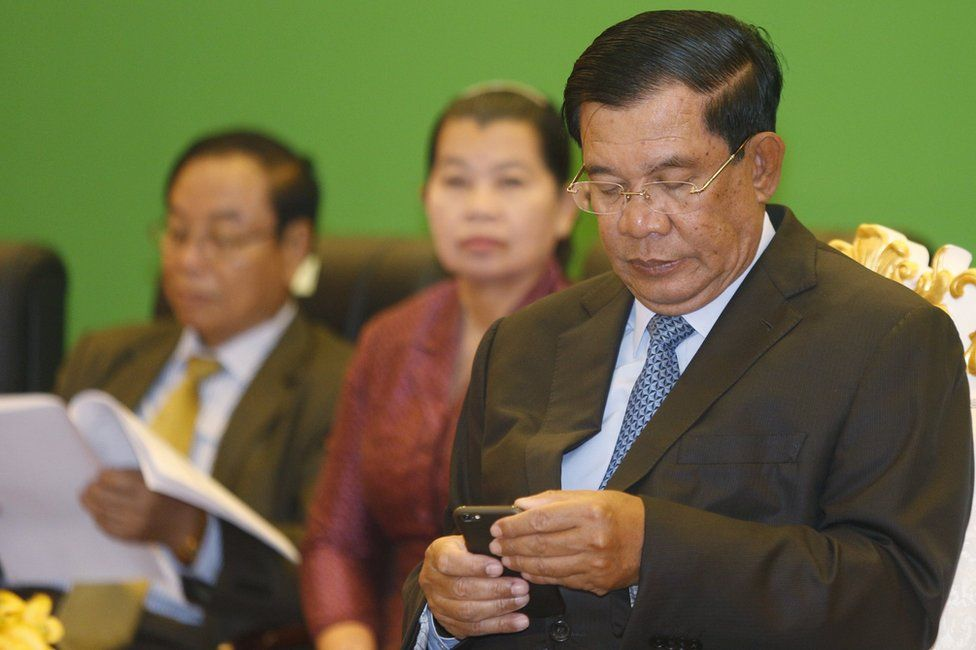 Cambodian Prime Minister Hun Sen checks his phone