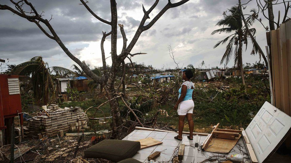 A lady stands on the remains of her damaged house in San Isidro, Puerto Rico after Hurricane Maria struck the island.