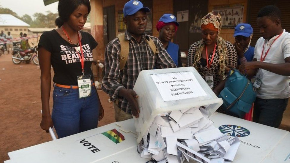 An electoral official overturns a ballot box prior to counting votes at a polling station in Tamale, northern region, on December 7, 2016.