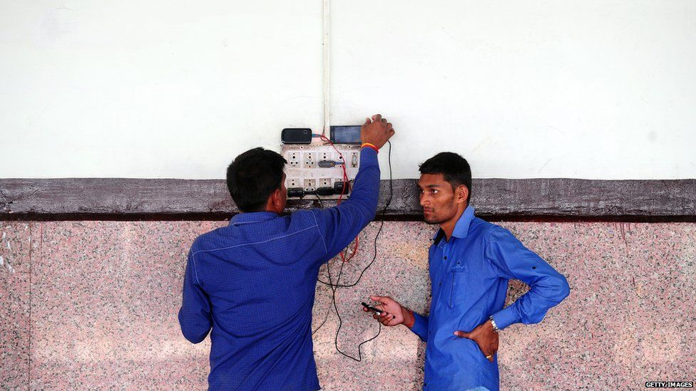 Phone charging at a station in India