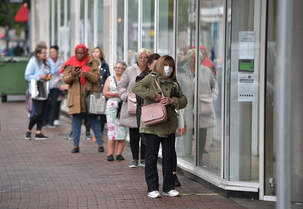Shoppers queue outside Dunnes Stores clothing shop on June 12, 2020 in Belfast, Northern Ireland. After being shuttered for months to curb the spread of Covid-19, retailers here reopened with social distancing measures, a few days ahead of when similar businesses can reopen in England.