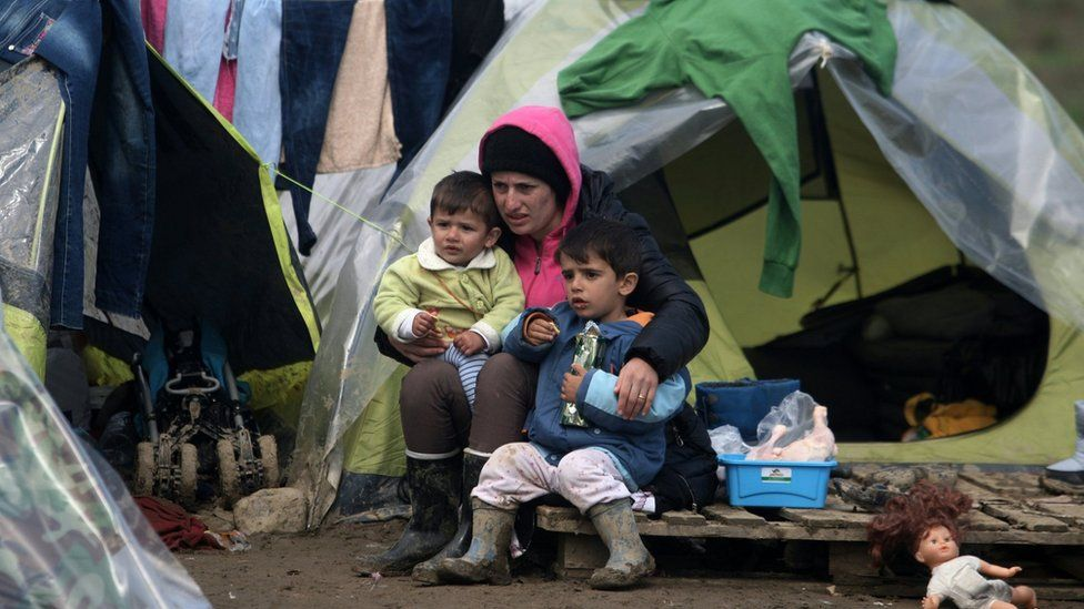 A woman and her children sit at a makeshift camp set by migrants and refugees at the Greek-Macedonian border, near the Greek village of Idomeni (March 17, 2016)