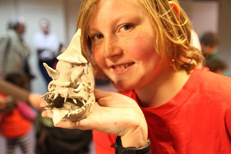 Child visitor to the exhibition holds sculpture of dragon-like thing made out of clay