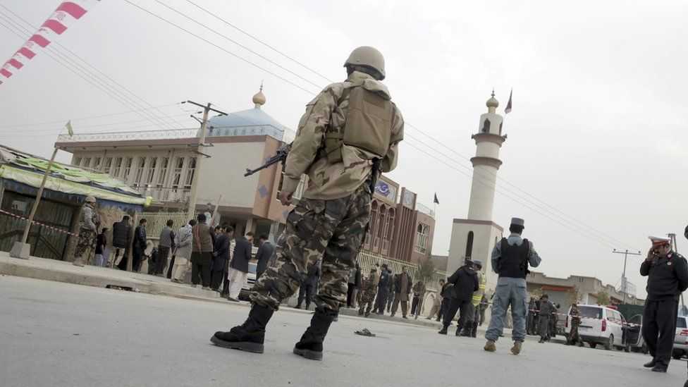 Afghan security forces and and civilians walk around the Shiite Baqir-ul Ulom mosque after a suicide attack inside it, in Kabul, Afghanistan, on 21 November 2016