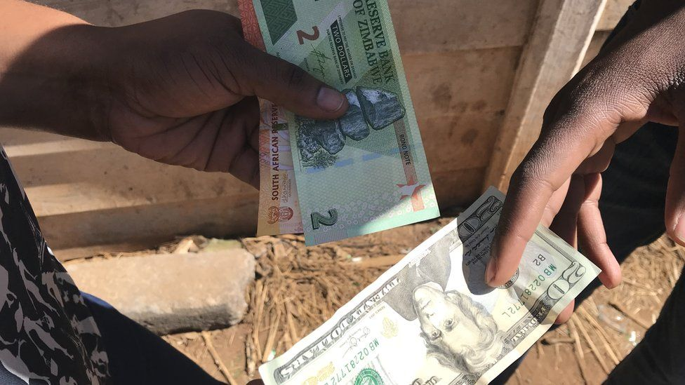 A money changer doing a deal with US dollars and Zimbabwean bond notes
