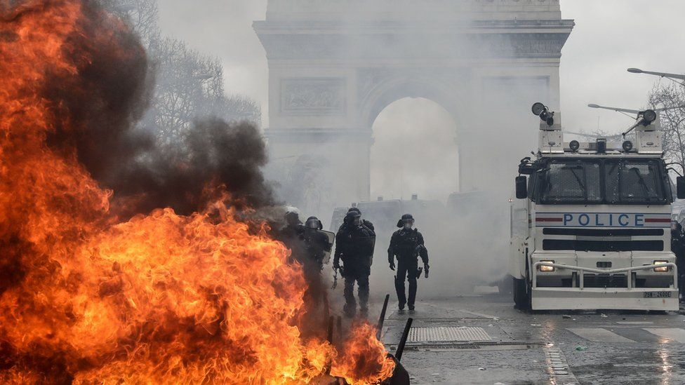 """French riot police forces stand behind a burning barricade on the Champs-Elysees in Paris on March 16, 2019, during the 18th consecutive Saturday of demonstrations called by the """"Yellow Vest"""" (gilets jaunes) movement."""