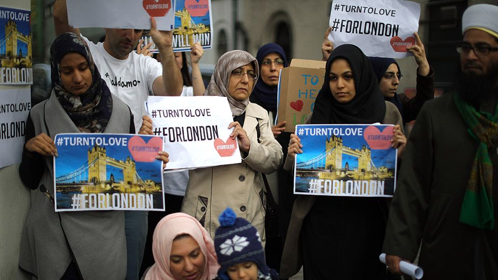 """Muslim women hold up """"turn to love"""" signs"""