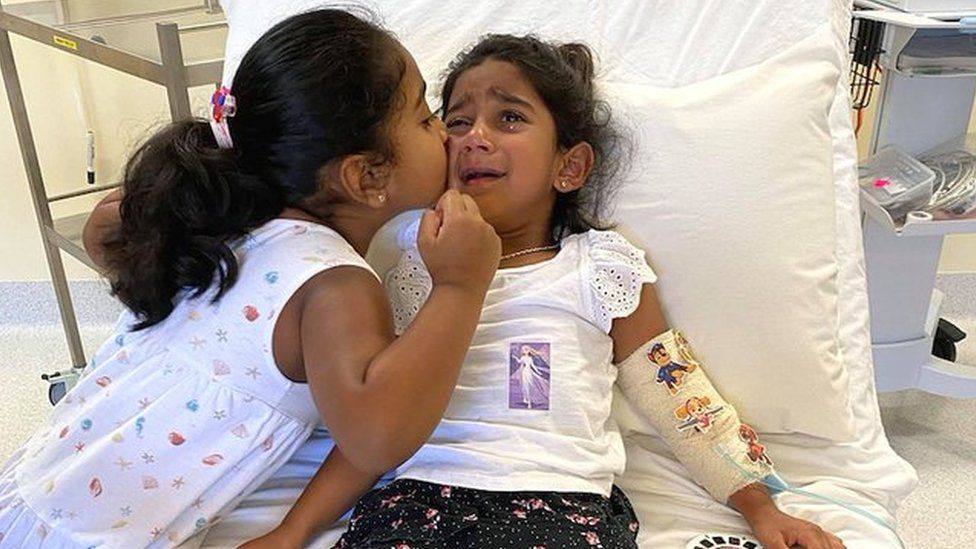 Tharnicaa crying on a hospital bed as her sister Kopika kisses her cheek to comfort her