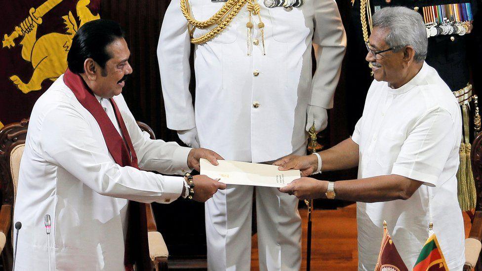 "Sri Lanka""s President Gotabaya Rajapaksa hands over a document to his brother and former leader Mahinda Rajapaksa,"