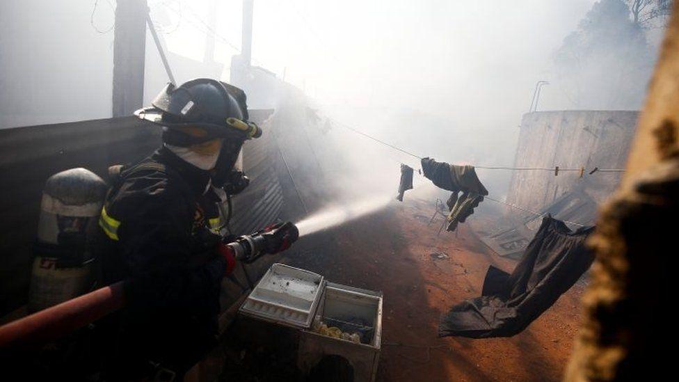 A firefighter tackles a blaze in Valparaíso. Chile. Photo: 24 December 2019