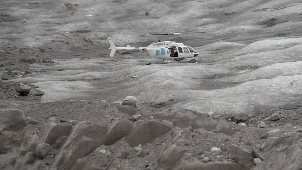 Helicopter flies over Sermilik glacier