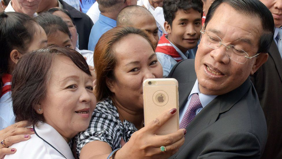Hun Sen poses for a selfie with supporters during